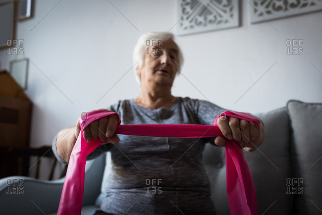 Senior woman performing exercise with resistance band in living room at home