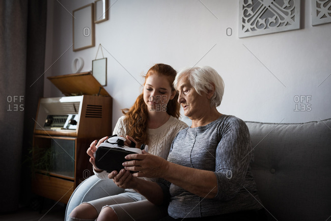Granddaughter assisting grandmother to wear virtual reality headset at home