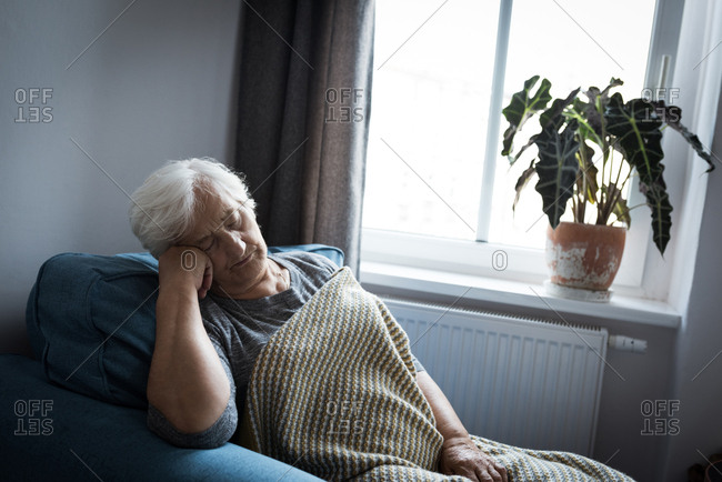 Senior woman relaxing on arm chair in living room at home
