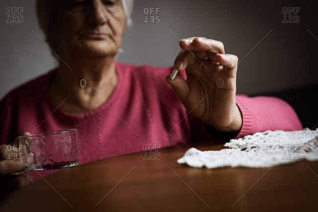 Mid section of senior woman looking at medicines in living room  at home