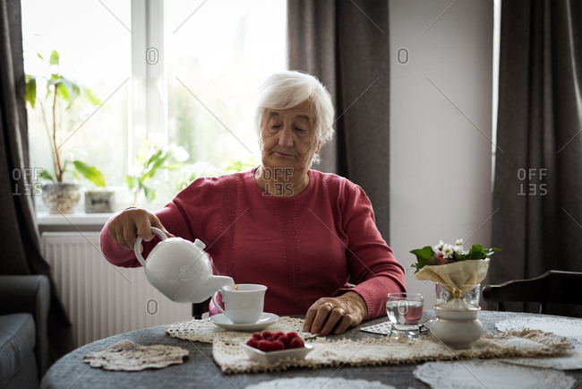 Senior woman pouring tea into cup from tea pot at home