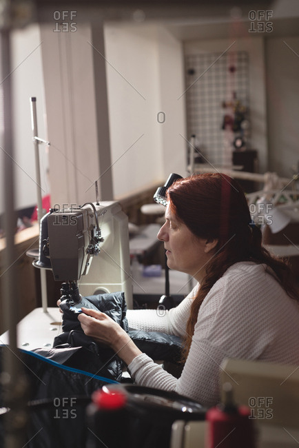 Tailor sewing cloth with sewing machine at tailor shop