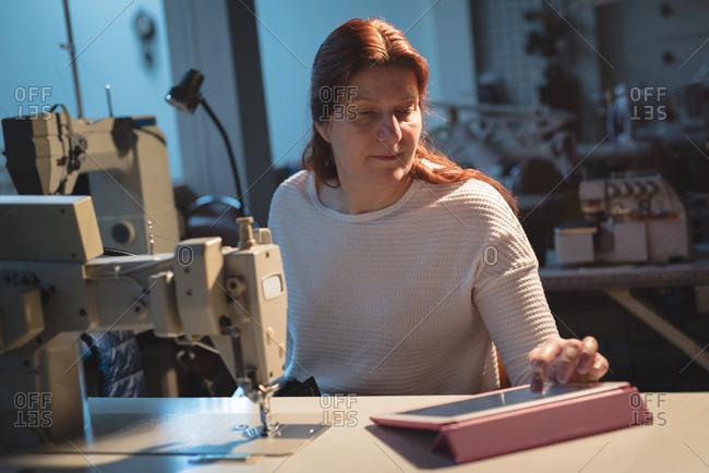 Tailor using digital tablet at workshop