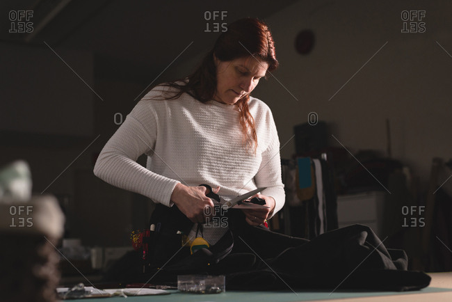 Tailor cutting clothes with scissors at workshop