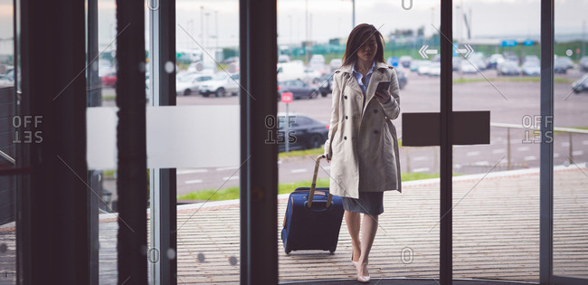 Sophisticated businesswoman using mobile phone while arriving in hotel