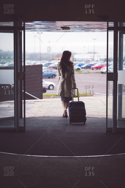 Rear view of businesswoman walking out of the hotel room with baggage