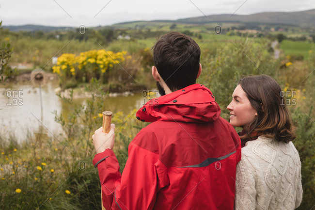 Couple interacting with each other near pond at countryside