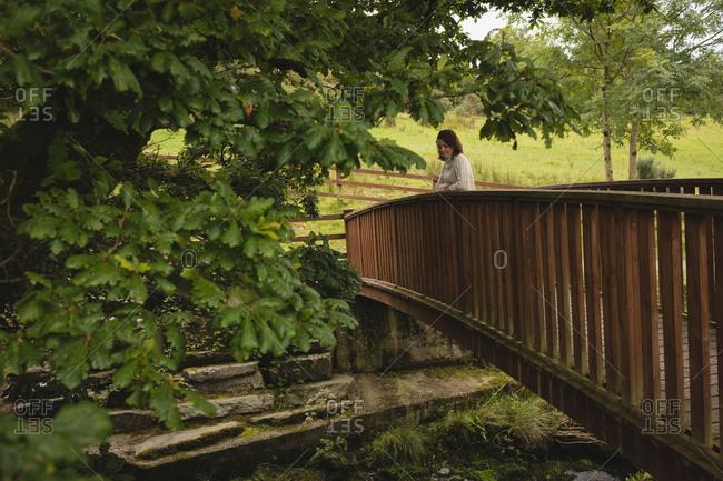Beautiful woman standing on footbridge at countryside