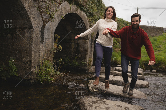 Happy couple running on the stone path in river