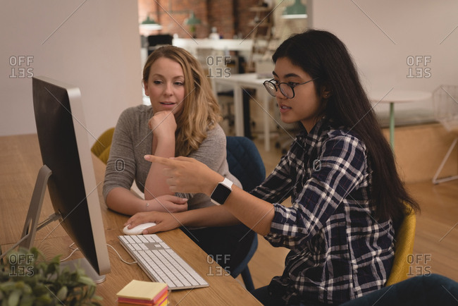 Female executives discussing over computer in the creative office