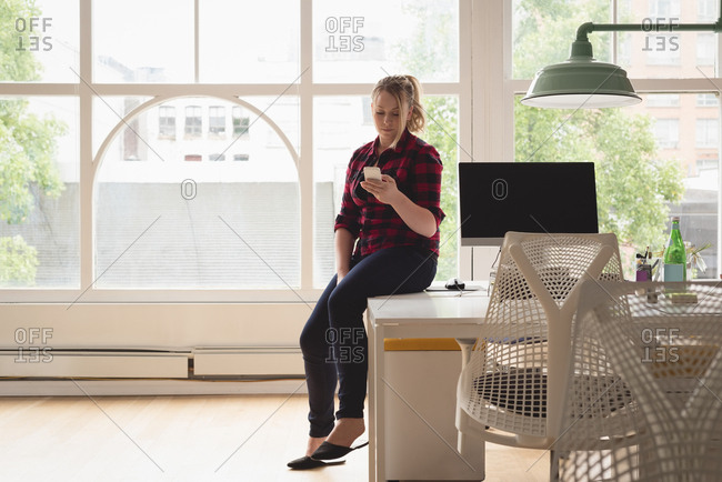 Female executive using mobile phone in the creative office