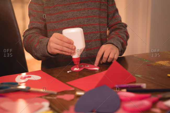 Mid section of boy preparing valentine card at home