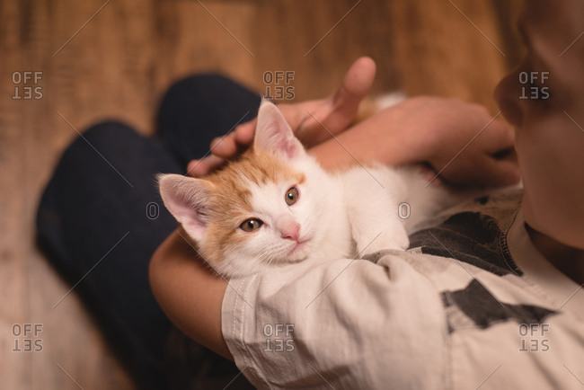 Boy holding her cat in living room at home