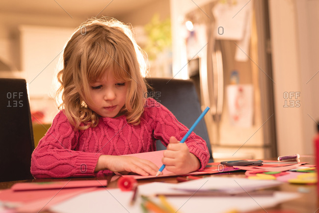 Adorable girl drawing on paper at home
