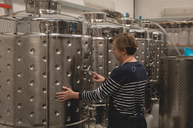 Female worker monitoring a pressure gauge of storage tank in brewery factory