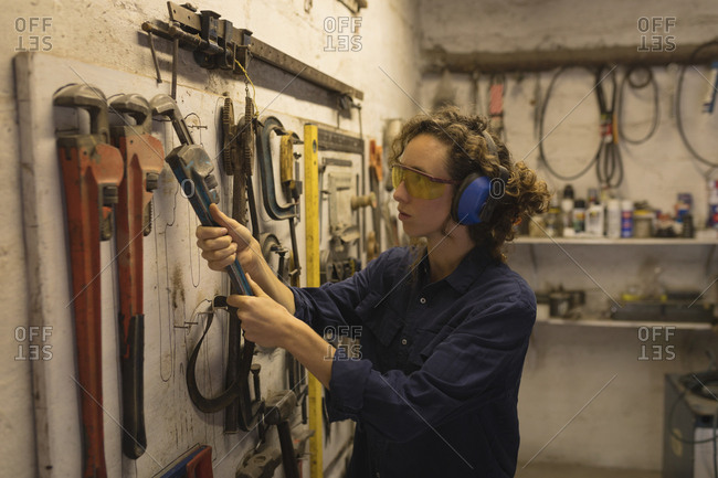 Female worker holding spud wrench in workshop