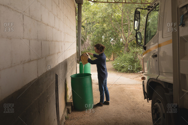 Woman pouring water into storage barrel in workshop