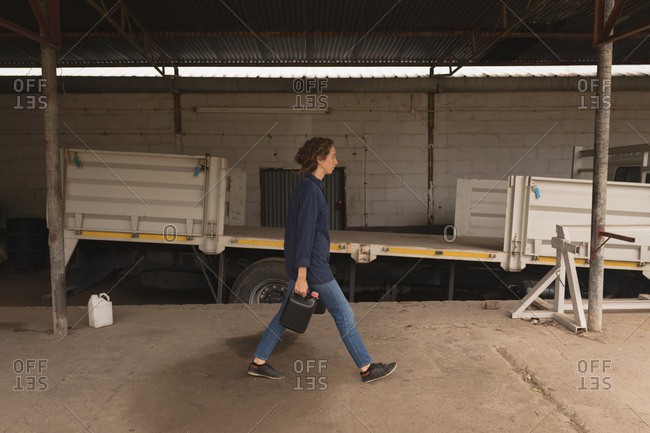 Female worker walking with can in the workshop