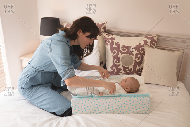 Cute little baby getting dressed by her mother on bed in the bedroom at home