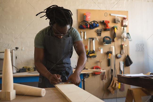 Carpenter measuring wooden plank in workshop