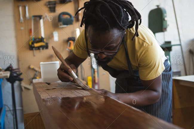Carpenter painting wooden plank in workshop