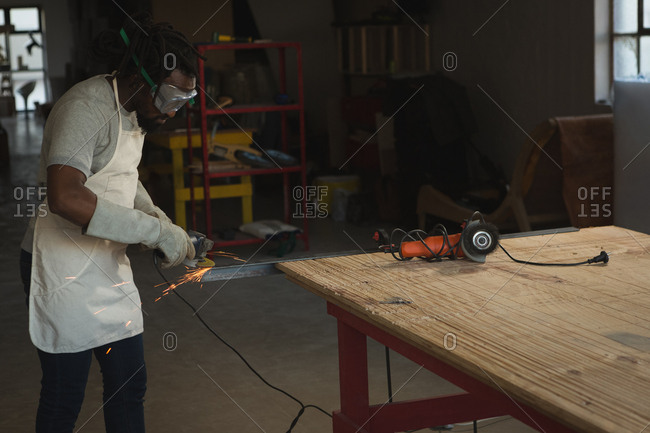 Carpenter cutting metal with electric saw in workshop