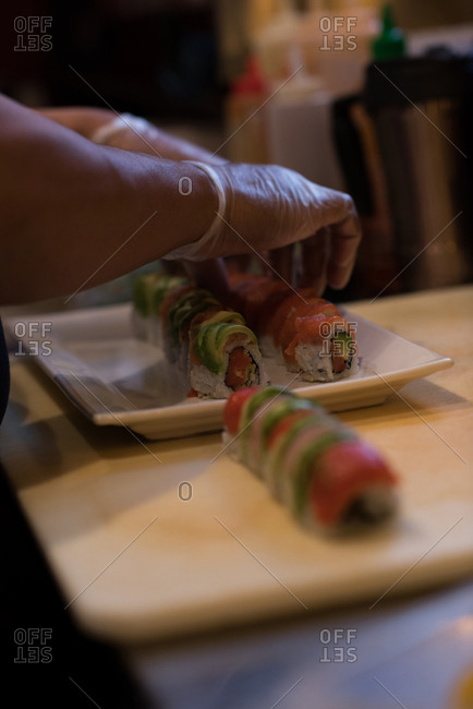 Chef preparing sushi on a tray in the kitchen