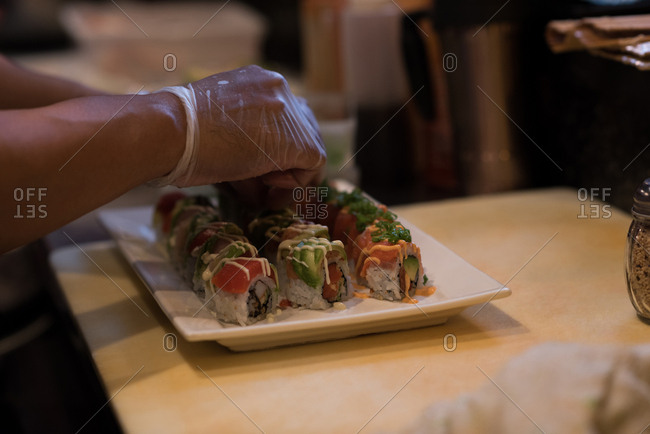 Chef garnishing sliced sushi in kitchen counter