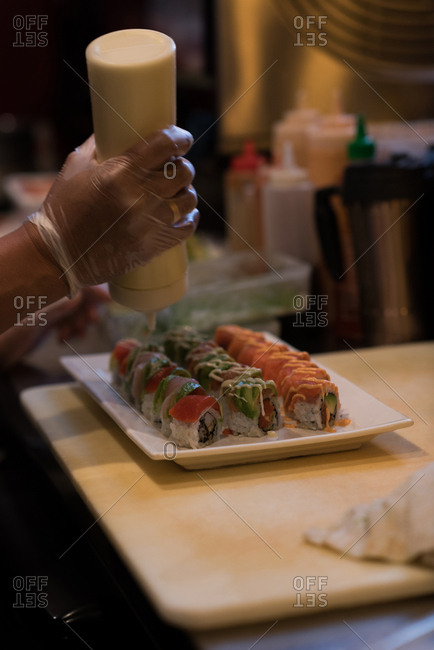 Chef adding mustard sauce over sushi in kitchen counter