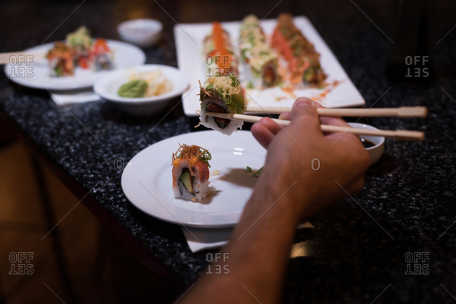 Man picking up sushi with chopsticks in a restaurant