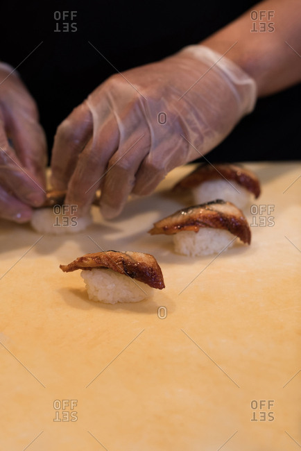 Chef preparing sushi on a chopping board in the kitchen