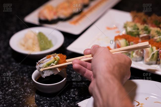 Man dipping sushi in soya sauce in a restaurant