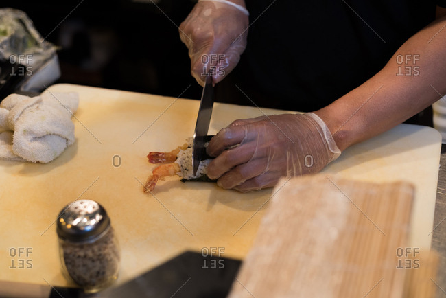 Chef slicing sushi roll on a chopping board