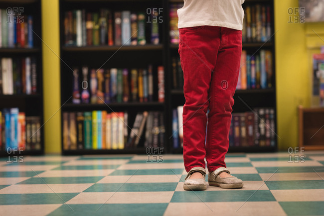 Low section of girl standing in book store