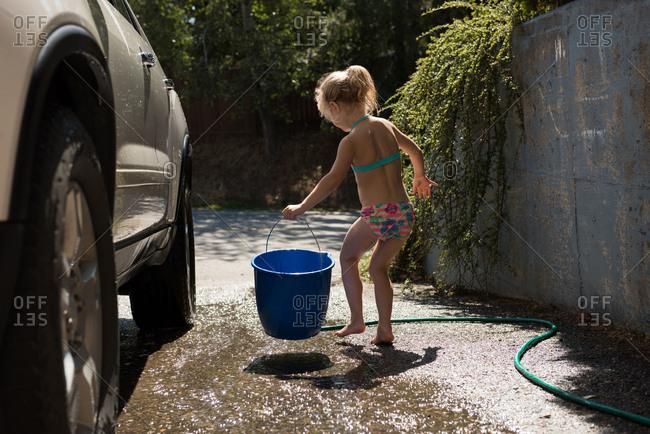 Girl holding blue bucket while washing car