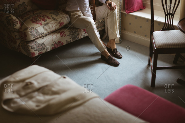 Mid section of groom wearing his shoes at home