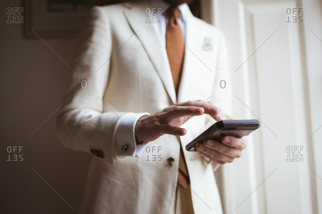 Mid section of groom using his mobile phone at home