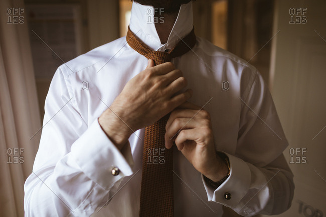 Mid section of man wearing the tie at home