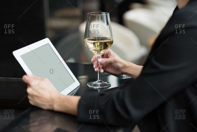 Mid section of businesswoman using a digital tablet and holding a champagne glass