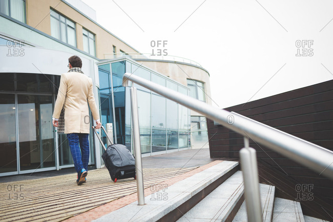 Rear view of businessman arriving in hotel on a sunny day