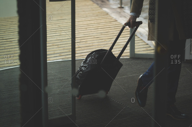 Businessman arriving in hotel with trolley bag