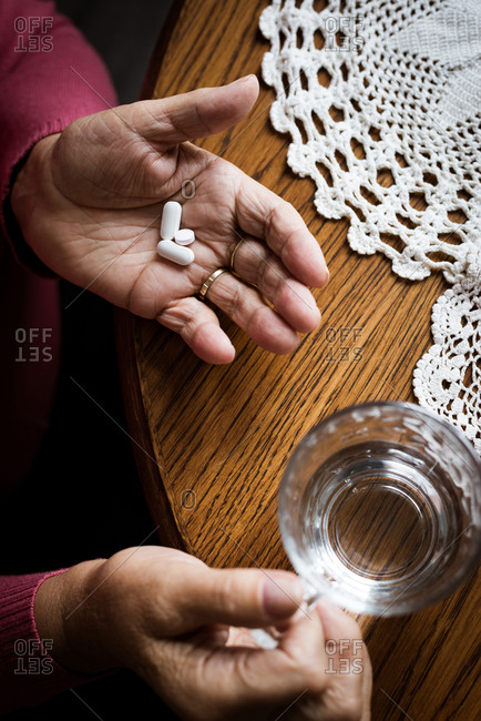 High angle view of senior woman taking medicines in living room at home
