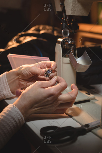 Close-up of tailor holding thread reel at workshop