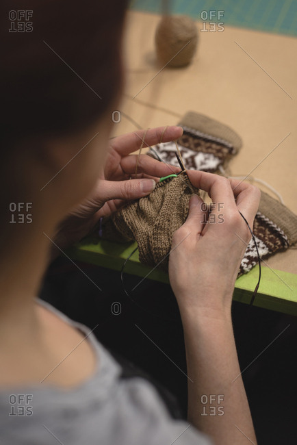 Close-up of woman knitting wool at tailor shop
