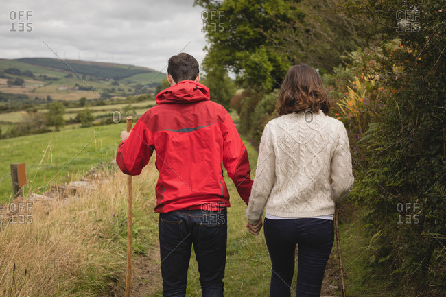 Rear view of couple walking with stick near countryside