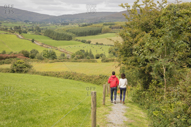 Rear view of couple walking on path near countryside