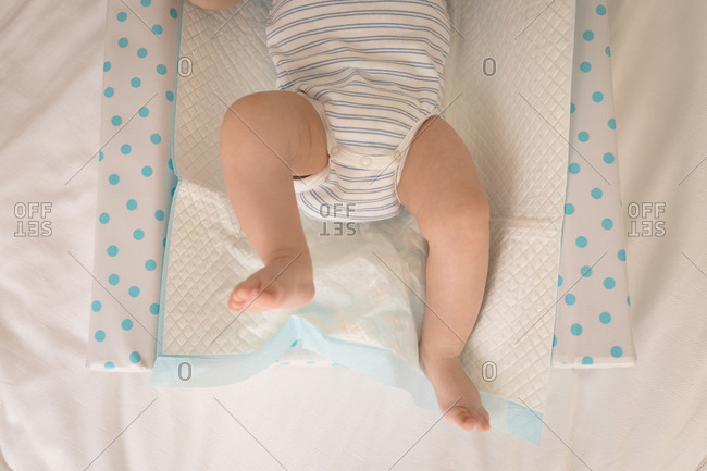 Close-up of baby in baby suit lying on bed at home