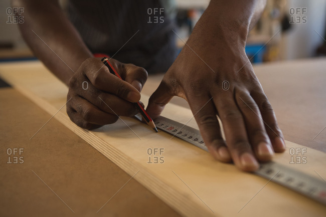 Mid section of carpenter measuring wooden plank with scale in workshop