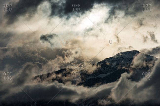 Mountain top surrounded with clouds at evening