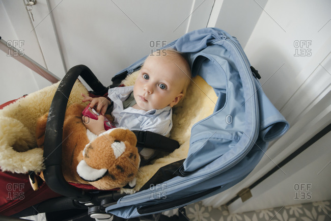Portrait of a blue eyed baby boy waiting in pram
